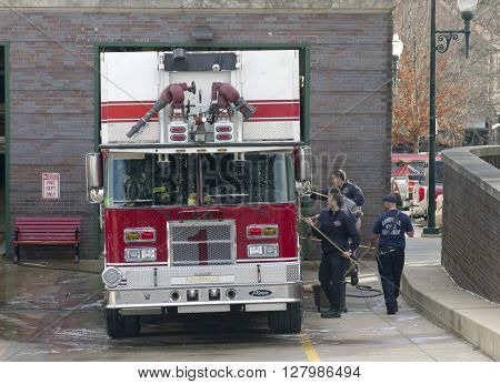 Asheville North Carolina USA - January 8 2016: A group of industrious firefighters wielding long handled brushes scrub down a firetruck at a Fire Station on January 8 2016 in downtown Asheville NC