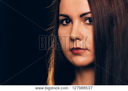 Portrait of a brunette woman with a deep look smiling discreetly- isolated on black.