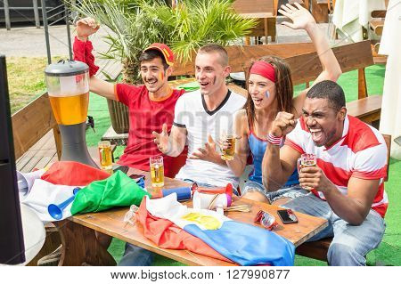 Young football supporter fans cheering with beer watching soccer match - Friends people with multicolored soccer tshirts and flags having fun - Sport championship concept - Warm afternoon color tones