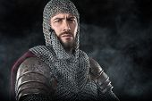 Portrait of Medieval Warrior with chain mail armour and red Cloak. Smoke Cloud on Dark Background poster