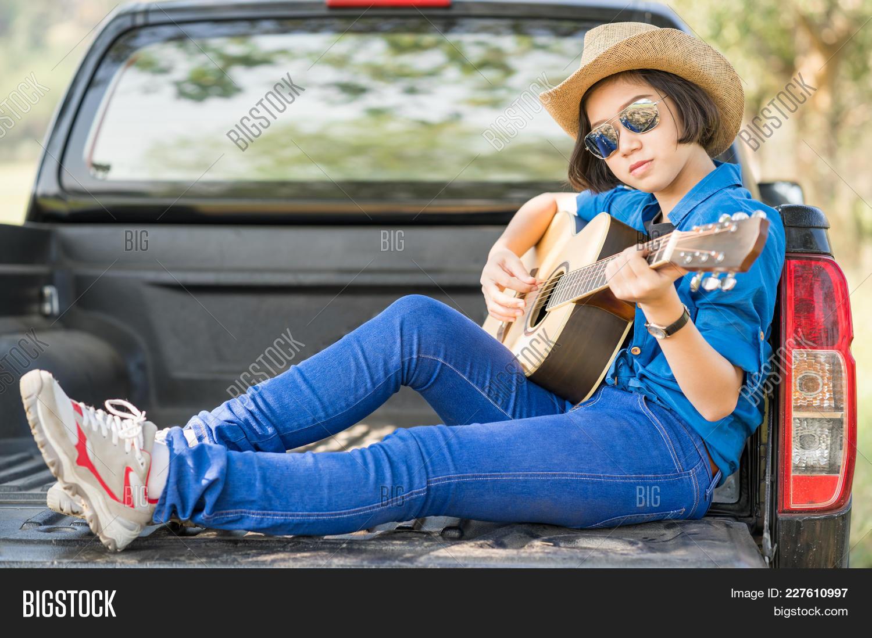 Young Asian Women Short Hair Wear Hat Playing Guitar  3e57eea44a75