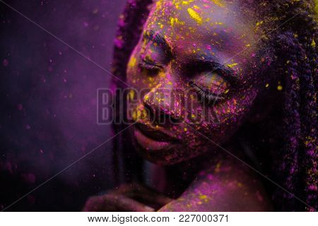 African woman with coloufrul powder on her face.