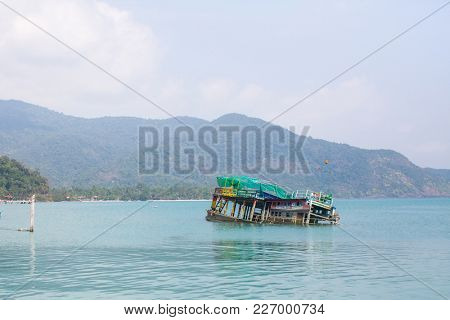 KO CHANG, THAILAND - FEB 15, 2018: Sunken ship near pier of Bang Bao fishing village, which consists of houses on stilts built into the sea. Ko Chang consisting of 8 villages with 5,356 inhabitants.