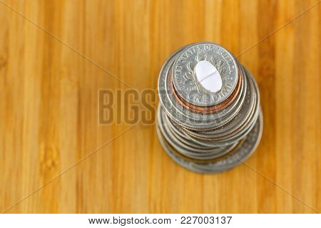 Anti anxiety white pill medicine on top of stack of American US coins on wooden background with copyspace