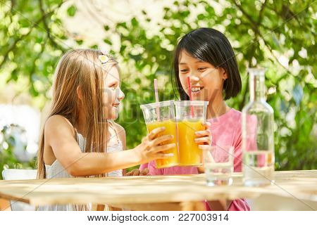 Two girls as girlfriends in kindergarten are poking with orange juice