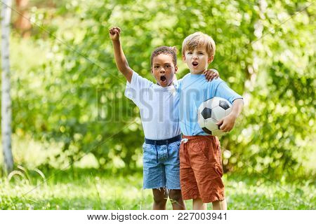 Two multicultural boys as friends with football cheer together