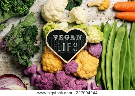 a heart-shaped signboard with the text vegan life placed on a pile of some different raw vegetables, such as cauliflower of different colors, broccolini, fava beans, french beans, kale or carrots