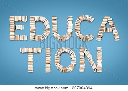 EDUCATION phrase formed from books, shot from above on light blue background