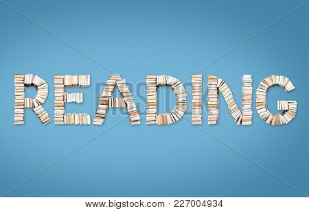 READING word formed from books, shot from above on light blue background