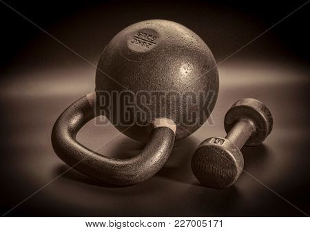 kettlebell and dumbbell on a black background - fitness concept, black and white sepia toned image