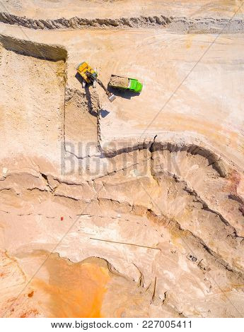 Aerial view of a excavator in the mine or construction site. Heavy industry and machinery. Industrial background on mining theme.