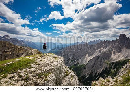 Hiker woman standing up achieving the top. National Nature Park Tre Cime In the Dolomites Alps. Beautiful nature of Italy.
