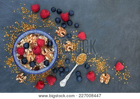Healthy macrobiotic breakfast with berry fruit, nuts, pollen grain, and granola with foods high in protein, antioxidants, minerals and vitamins on slate background, top view.