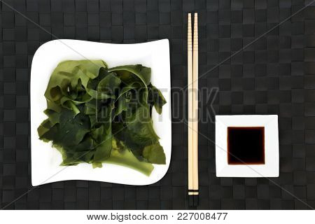 Japanese wakame seaweed health food with low sodium soy sauce on porcelain dishes with chopsticks. Has many benefits for a healthy life and is very high in minerals.