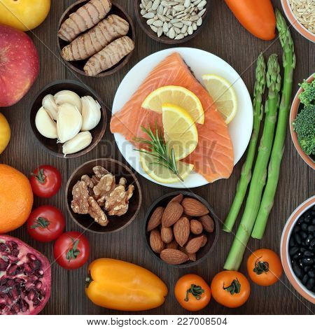 Heath food high in nutrients with fresh salmon, vegetables, fruit, herbs, spices, nuts and seeds. Concept of super foods with omega 3 fatty acids, minerals, vitamins and antioxidants.