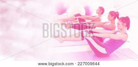 Class stretching on mats at yoga class in fitness studio against glowing background