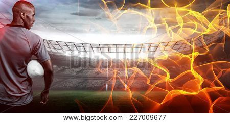 Abstract orange glowing black background against rear view of sportsman with rugby ball