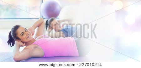 Two fit young women doing pilate exercises against glowing background