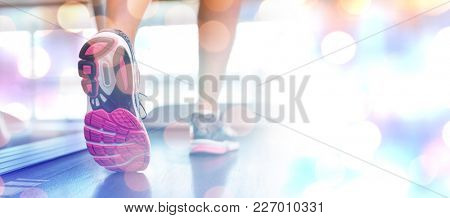 Womans feet running on the treadmill against glowing background