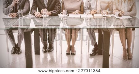 Panel of corporate personnel officers sitting at table in office