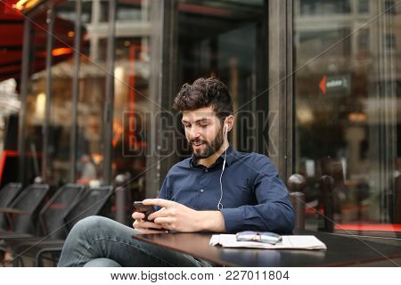 Student Dressed In Blue Shirt Listening To Music With In Ear Headphones And Smartphone. Young Happy