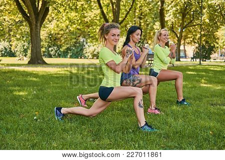 Three Positive Sporty Female Doing Squats In An Autumn Park.