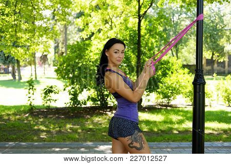 Brunette Sporty Female Exercising With Fitness Trx Straps In Summer Park.