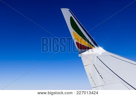 Plane wing in clear and blue sky with Ethiopian flag elements on it