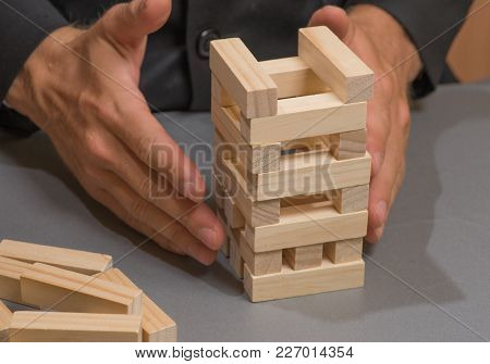 Hands Of A Businessman Built From Wooden Blocks.