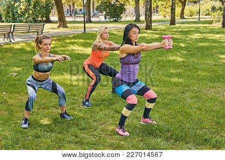 Three Sporty Women In Colorful Sportswear Doing Squats In A Park.