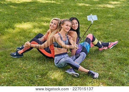 Three Attractive Sporty Women Making Selfie After Fitness Workouts In A Park.