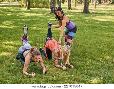 Sporty Female Teaching Two Women Legs Workout In A Park.