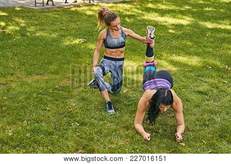 Sporty Female Teaching A Woman Legs Workout In A Park.