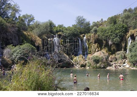 Ljubuski, Bosnia And Herzegovina - August 16 2017: People Bathing In The Natural Park Of Kravice Wat