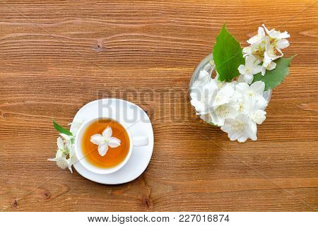 White Mug Of Green Tea And A Vase With Jasmine. Wooden Table. Top View