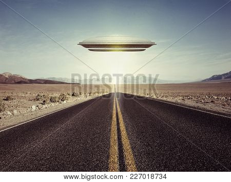 3d Illustration Of A Ufo Over An Empty Desert Road