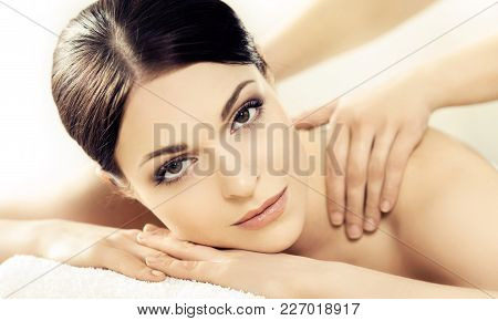 Portrait Of A Girl In Spa. Massaging Therapy Procedure. Skin Care And Face Lifting Concept.