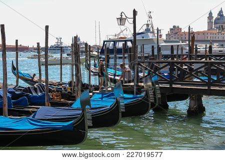 Venice, Italy - August 13, 2016: Tourists Choose The Gondola At The Pier