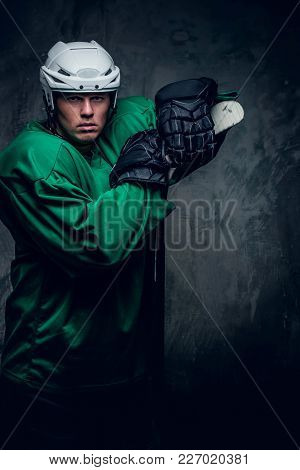 Portrait Of A Hockey Player In Protective Clothes Holds Playing Stick On Grey Background.