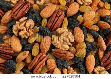 Food Background - Big Peeled Almonds, Peeled Walnuts, Peeled Pecan Nuts, Big Dark Blue Raisins And Y