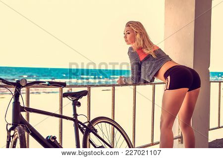 Sexual Blond Female From Her Back Posing With Bicycle On A Beack In A Day Light.