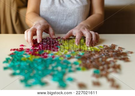 Woman hand sorting car electric parts colorful mini fuses on desk. Soft focus.
