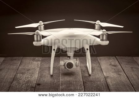 FORT COLLINS, CO, USA - FEBRUARY 23, 2017:  DJI Phantom 4 pro quadcopter drone with a camera  on a rustic wooden table, black and white sepia toned image.