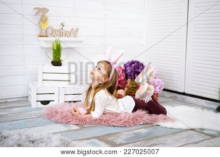 Four Years Old Happy Girl With Bunny Ears Lying Around Easter Decorations On White Background