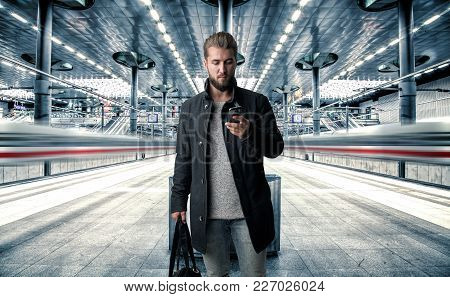 Attractive Man With A Smart Phone In His Hand Is Standing At The Platform Waiting For The Train