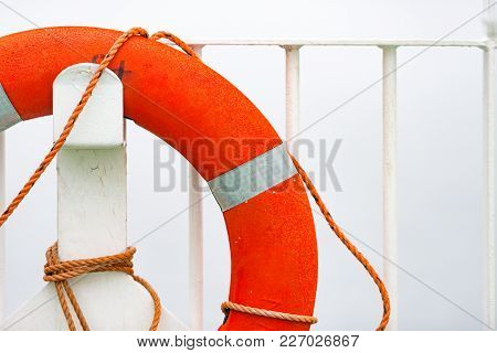 Orange Lifebuoy On White Wall In Port. Norway, Scandinavia, Europe.