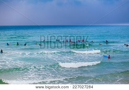 Surfing School Class Taking Place In The Water At Sunset