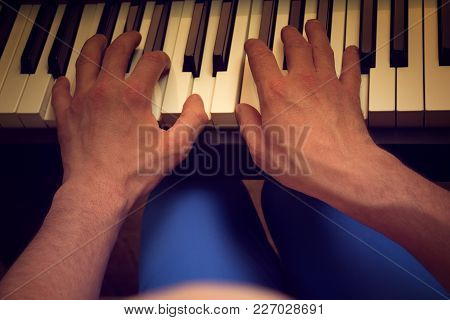 A Man In Blue Trousers Plays A Piano On A Dark Background