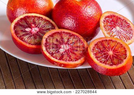 Sicilian Oranges In A White Plate On A Wooden Striped Background