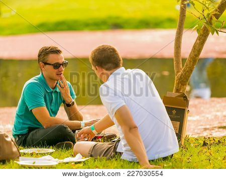 Johannesburg, South Africa, 05/09/2015,  Gay Couple Lying On The Grass At The Winter Sculpture Fair